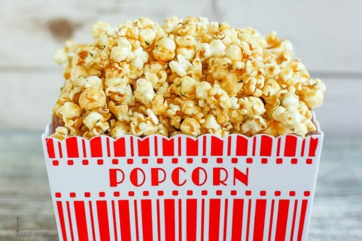 A overflowing popcorn container piled high with Lemon Thyme Caramel Corn.
