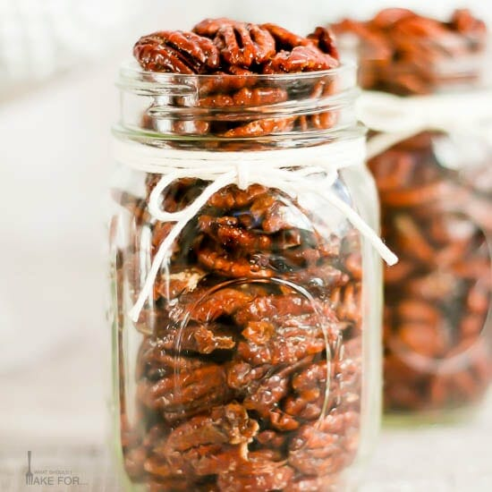 Candied pecans in a mason jar with a white string tied in a bow.