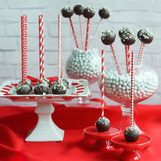 Chocolate Peppermint Cake Pops displayed on cake plate and vases on a red table cloth