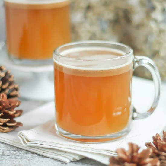 Hot Buttered Rum in a glass mug with a frothy top.