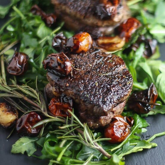 Close up shot of Filet Mignon with Balsamic Tomatoes on a bed of arugula.