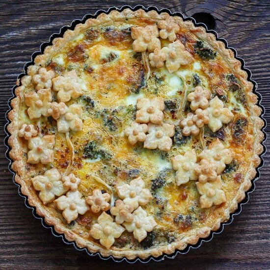 Roasted Broccoli Quiche in a fluted pan decorated with little pastry flowers.