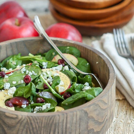 Spinach Salad with Poppy Seed Dressing in a wood bowl with apples in the background.