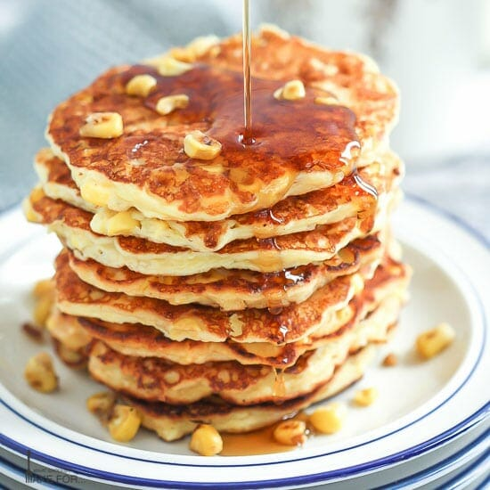 A stack of Corn Pancakes piled on a stack of white an blue plates with corn kernels scattered on top and big drizzle of syrup being poured over.