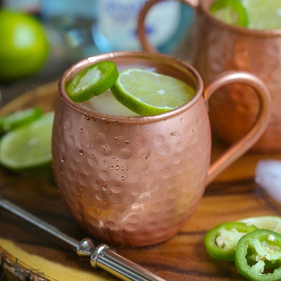Close up shot of a Mexican Mule served in a copper mug garnished with lime and jalapeño slices placed on a wood board with another mug in the background.