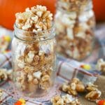 Autumn Caramel Popcorn in a mason jar and scattered around on a plaid towel with candy corn.
