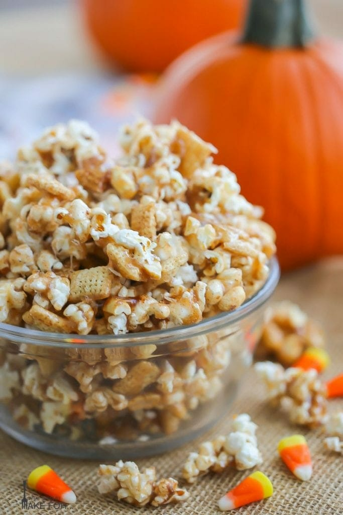 Autumn Caramel Popcorn in a glass bowl with caramel corn and candy corn scattered on a burlap covered table.