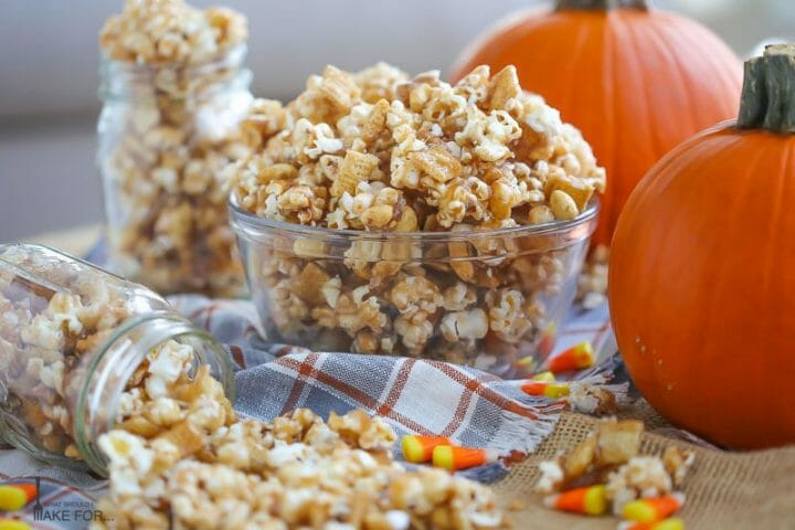 Autumn Caramel Popcorn in a glass bowl and spilling out of a mason jar on a plaid towel with candy corn scattered around next to pumpkins.