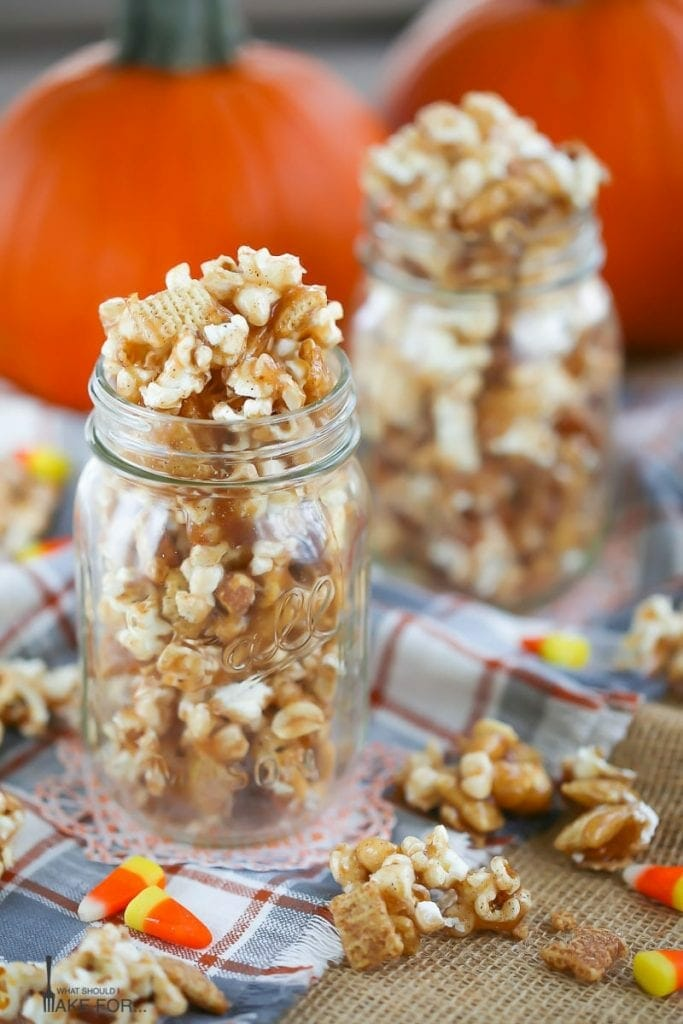 Autumn Caramel Popcorn in glass mason jars on a plaid towel with caramel corn and candy corn scattered around.