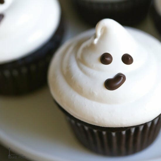 Close up of an easy ghost cupcake with marshmallow frosting and a cute chocolate face!