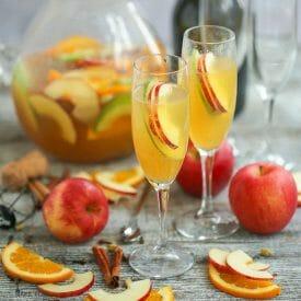 Sparkling Autumn Sangria served in two champagne flutes with apple slice garnishes with a pitcher of sangria in the background and fruit garnishes scattered on the table.
