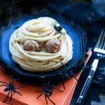 A Spooky Spaghetti Mummy on top of a black plate and stack of orange napkins with plastic spiders scattered around for decoration.