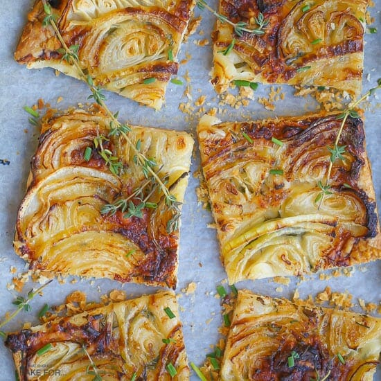 French Onion Tart cut into square slices, golden brown, and scattered with thyme sprigs.