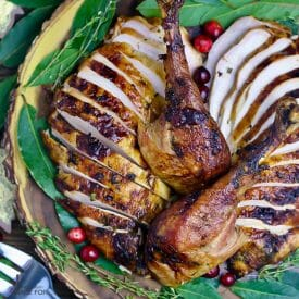 Overhead shot of Garlic and Herb Roast Turkey , carved, sliced and on an wooden platter with fresh bay leaves and loose cranberries.