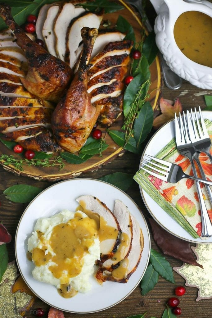 Garlic and Herb Roast Turkey with Cider Pan Gravy, carved and sliced on a wooden platter with fresh bay leaves and loose cranberries. A serving of turkey and mashed potatoes with gravy is next to the turkey.