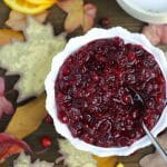 Overhead shot of Orange Cranberry Sauce in a pretty white bowl with fall leaves and fresh cranberries scattered around.