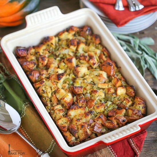 Pancetta and Leek Stuffing baked in a rectangle pan with crispy, buttery edges. The pan is placed on a autumn napkin, with a serving spoon and herbs alongside.