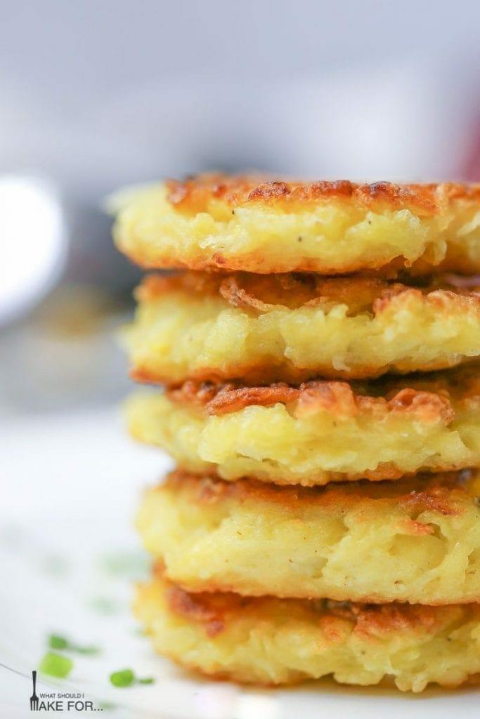Mini Potato Latkes stacked up in a close up shot.