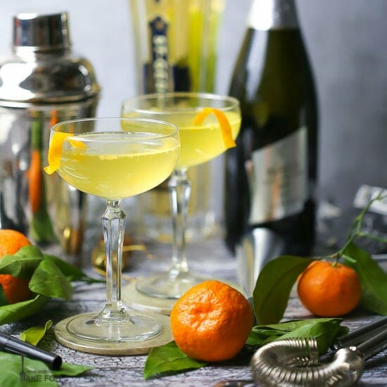 Sparkling Orange and St-Germain Cocktails are served in coupe glasses with orange peel twists, with clementines, silver noisemakers, and bar accessories scattered around.