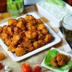 Buffalo Cauliflower Bites with Blue Cheese Dip served on a white square platter with celery stalks and a beer in the background.