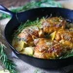 A cast iron skillet with crispy chicken thighs in creamy lemon and herb sauce.