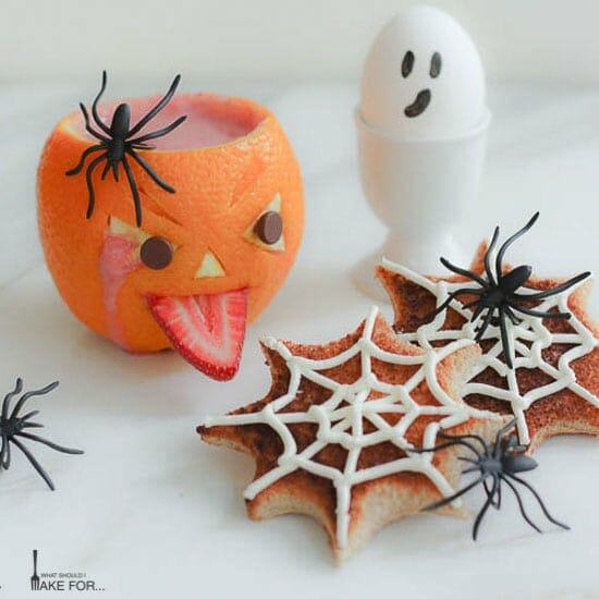 A spooky Halloween breakfast display: a decorated orange jack o'lantern filled with a strawberry smoothie, spiderweb decorated toast, and a ghostly hard boiled egg.