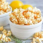 A close up of a bowl of Lemon Thyme Caramel Corn with lemons in the background and fresh thyme scattered in front.
