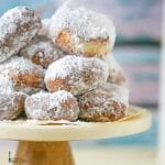 New Orleans Beignets piled on a parchment lined cake stand.