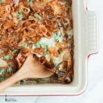 Creamy green bean casserole topped with crispy fried shallots in a rectangle baking dish with a wooden spoon scooping out a serving.