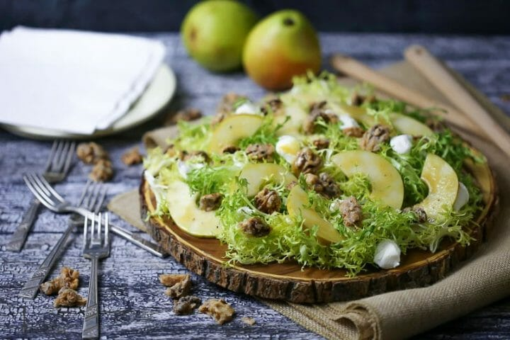 Pear Frisée Salad with Candied Walnuts and Goat Cheese served on a round wooden cutting board with two anjou pears in the background and forks scattered around.