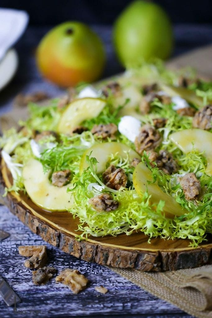 Pear Frisée Salad with Candied Walnuts and Goat Cheese served on a round wooden cutting board with two anjou pears in the background.