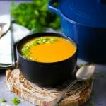 A bowl of carrot ginger soup garnished with scallions on a wood coaster with a blue pot, herbs and spoons in the background.