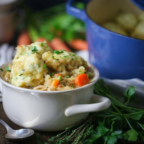 A serving of Chicken and Herb Dumplings in a white crock with carrots, peas and chicken.