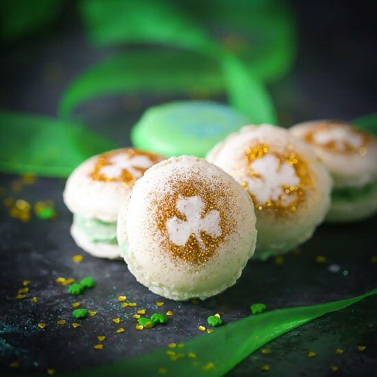 Close up of Shamrock Macarons decorated with gold glitter shamrocks and green ribbon in the background.