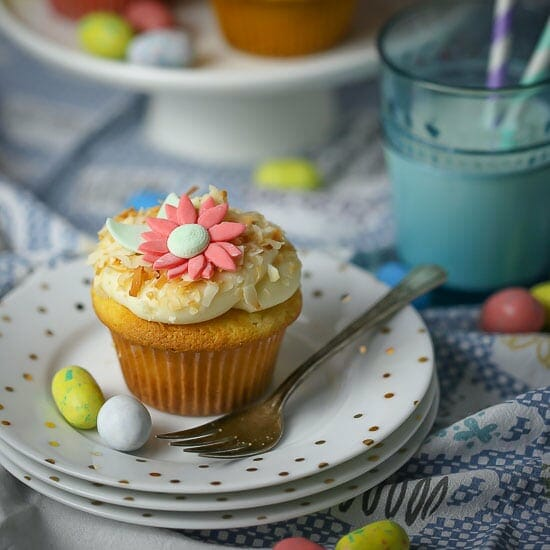 Toasted Coconut Cupcakes on a stack of polka dot plates with two candy eggs.