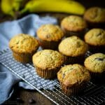 Chocolate Chip Banana Muffins on a wire rack with bananas in the background.