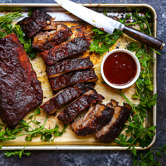 Baby Back Ribs with Bourbon BBQ Sauce on a sheet tray with herbs, sauce and cut with a knife.