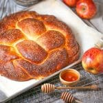 A braided round apple challah bread sweetened with apples and honey.