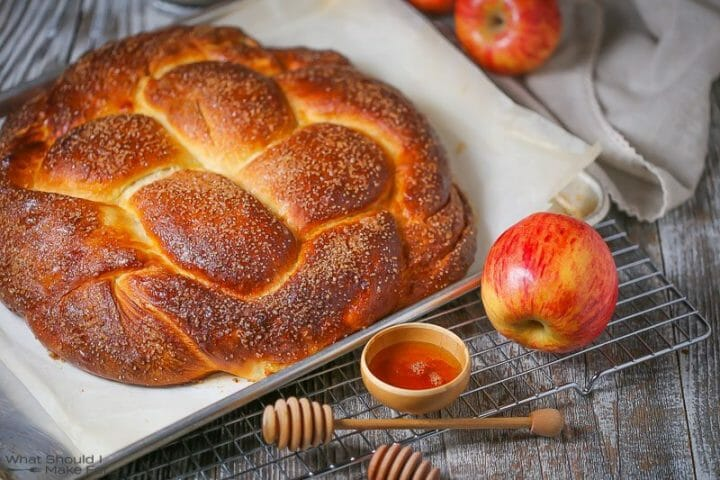 A close up of a golden brown round loaf of apple challah bread served with apples and honey for Rosh Hashanah.