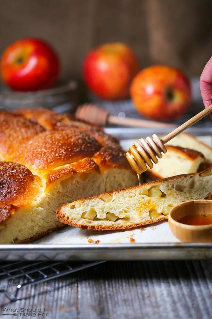 Drizzling honey over a slice of apple challah bread. The slice of bread is studded with apple chunks.