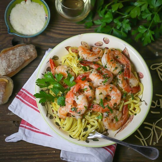 Easy Shrimp Scampi in a bowl with parm and bread served alongside.