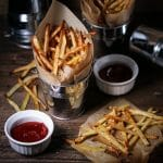 Oven fries in paper-lined metal serving bucket served with spicy sriracha ketchup.