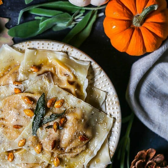 Butternut Squash Ravioli with pumpkins and sage leaves around.