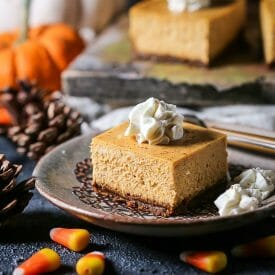 A serving of a Pumpkin Cheesecake Bars is served on a plate with a doily with pine cones, pumpkins, cinnamon sticks, and candy corn scattered around on the table.
