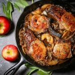 Close up of apple cider pork chops cooked with caramelized apples, onions and sage.