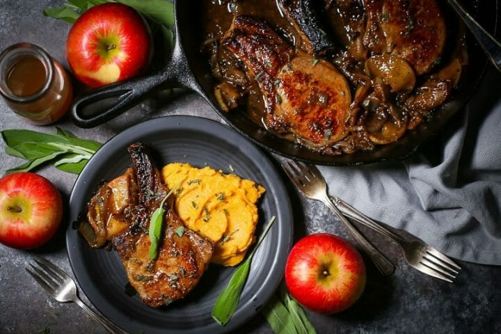 Apple cider pork chop plated with butternut squash mash surrounded by apples and sage.