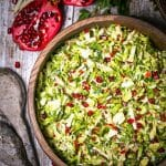 Brussels Sprouts and Pomegranate Salad served in a round wood bowl with pomegranate and apple slivers scattered around on the table.