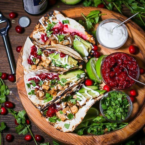 Four Leftover Turkey Tacos on a round wooden tray with cranberry chutney, minced cilantro and sour cream in small bowls with whole cranberries and cilantro scattered around.