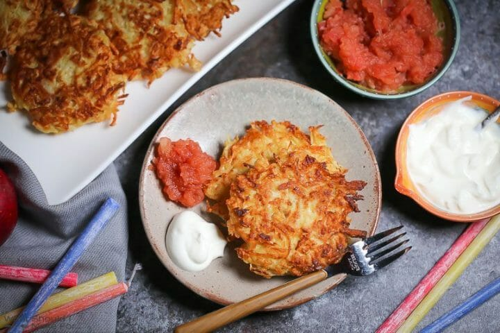 Two Celery Root Latkes on a small plate served with apple sauce and sour cream.