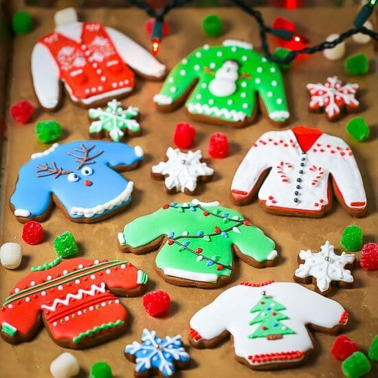 Ugly Sweater Cookies are decorated with lights, christmas trees, snowmen, and candy canes and are scattered on a tray with gum drops and mini snowflake cookies.